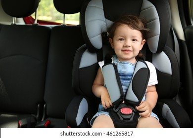 Boy sitting in a car in safety chair