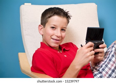 A boy sitting in a chair, holding an electronic video game device.