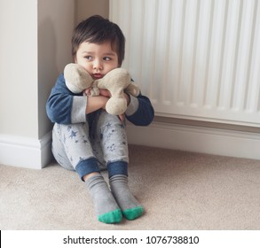 A boy sitting in the corner and cuddling teddy bear with scared face from bad dream or nightmare .Unhappy Child sitting on floor in corner and looking out, Toddler boy wall corner punishment sitting.