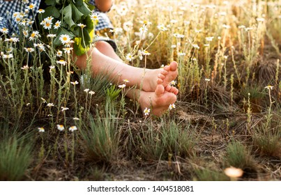 the boy is sitting in a daisy field with bare legs