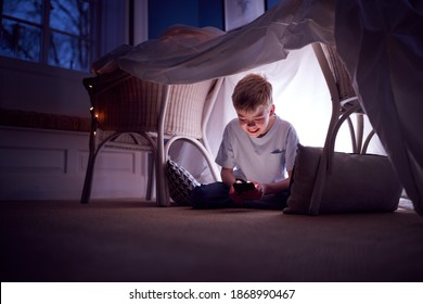 Boy Sitting In Den Or Camp He Has Made At Home Playing With Mobile Phone - Shutterstock ID 1868990467