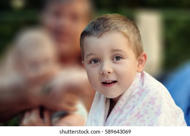 Boy is sitting in the garden after swimming wrapped in a towel