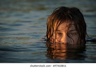 A boy sitting half submerged in the water at sunset.