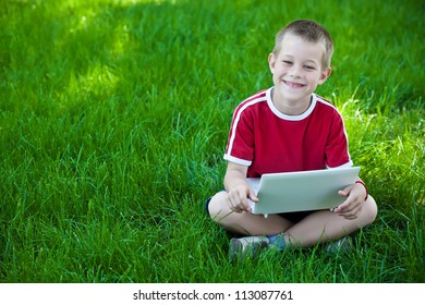 boy sitting with a laptop on the grass