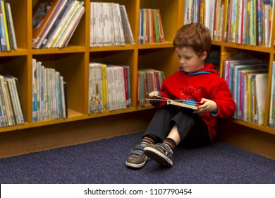 Boy sitting in a library looking at book in front of book shelves