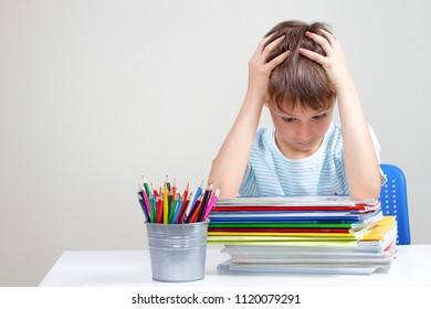 The boy sitting and looking in to books and notebooks. Education, school, learning difficulties concept