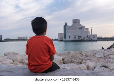 A boy sitting and looking at Museum Of Islamic Art Doha, Qatar.