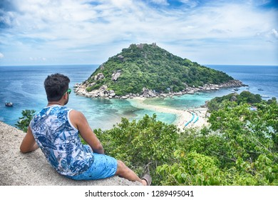 A boy sitting and looking towards the beautiful small island amid blue sea waters (Koh Nang Yuan Islands) in afternoon time