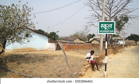 boy sitting near board written Hindi language - School   Daldali Village Rural India Dhanbad / Jharkhand state of India / at Jharkhand / India clicked on 10 February 2018