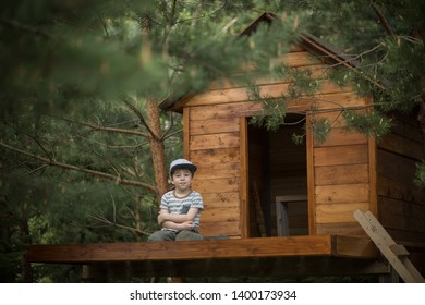 A boy is sitting near his new handmade tree house. Image with selective focus and toning.