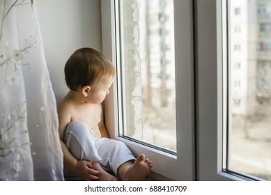 Boy sitting near the window. A boy in white pants. He is holding a teddy bear.