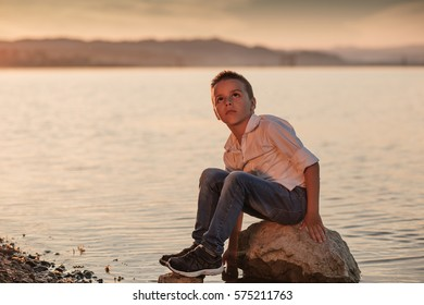 boy sitting next to lakes and resting in the twilight days, summer colors and atmosphere