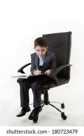 boy sitting in an office chair pretending he's working very hard