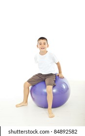 Boy sitting on big ball against white background