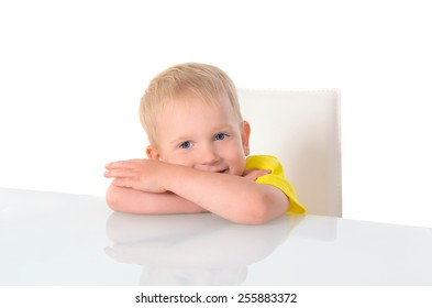 boy sitting on chair at the table, his head resting on his hands