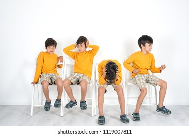 The boy is sitting on a chair and waiting for his turn.  He is very impatient, he is suffering