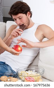 Boy sitting on couch prefers chocolate than apple