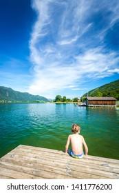 Boy sitting on a dock at Ossiacher Lake, Carinthia, Austria
