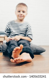 Boy sitting on the floor at home and smiling. Concept of healthy feet, and flat feet treatment. Children's health. Unfocused portrait of cute 6 year old boy. Focus on feet.