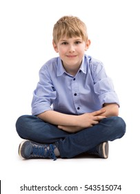 BOY SITTING ON THE FLOOR AND LOOKING AT THE CAMERA ISOLATED ON WHITE BACKGROUND, PORTRAIT OF SCHOOL KID