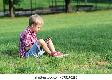 boy sitting on grass and play with tablet pc