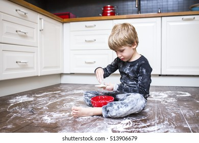 A boy sitting on the kitchen floor and playing with flour.