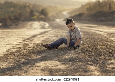boy sitting on the road and playing with stones