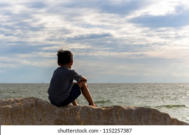 Boy sitting on rocks looking at the sea.