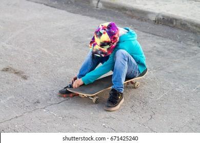 A boy is sitting on a skateboard