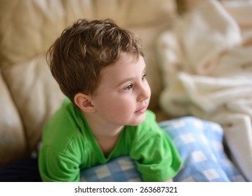 Boy sitting on sofa watching TV