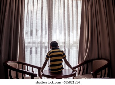 Boy sitting on a table looking down down
