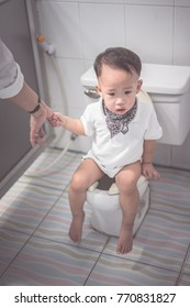 A boy is sitting on toilet with suffering from constipation or hemorrhoid.
