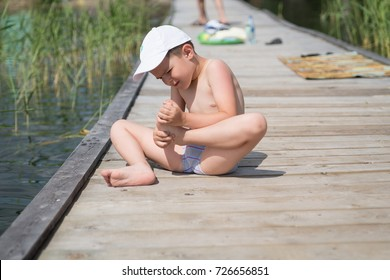 A boy sitting on a wooden floor, looking for a splinter in his foot.