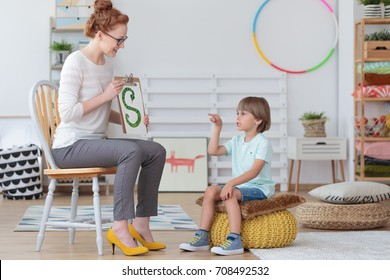 Boy sitting on a yellow pouf practicing correct pronunciation during a lesson with speech therapist