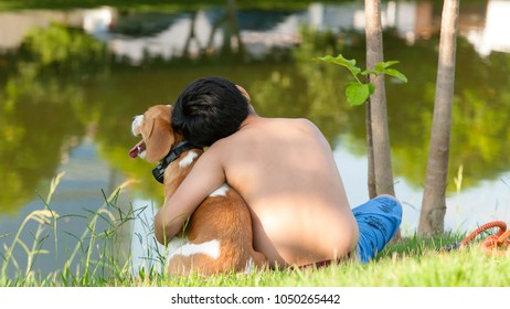 boy sitting in a park hugging his brown and white bicolor beagle puppy on a sunny day with a lake in front of him