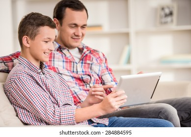 Boy sitting at sofa at home with father and using laptop.