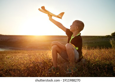 boy sitting at sunset with an airplane in his hand