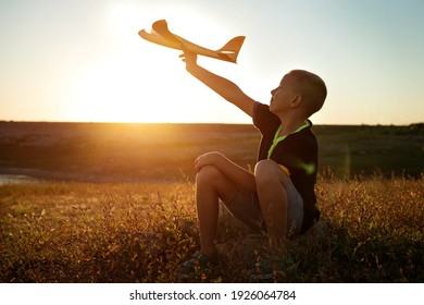 boy sitting at sunset playing with an airplane in his hand in summer outdoors