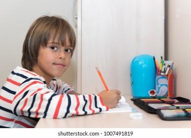 Boy sitting at table, writing, finishing homework