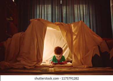 A boy is sitting in a tepee tent at night with a light, books and teddy bear.