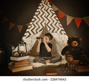 A boy is sitting in a tepee tent at night with  a light, books and teddy bear. He is looking up with a monocular for a exploration or camping concept.