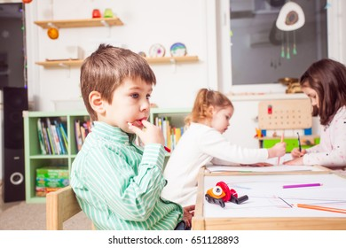 Boy is sitting and thinking what to draw in kindergarten