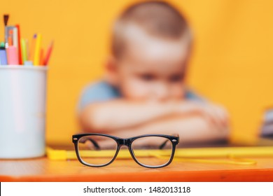 boy sitting ubfocused glasses in focus. Concept problem of ophthalmology correction of myopia. back to school. Selective focus. upset child.