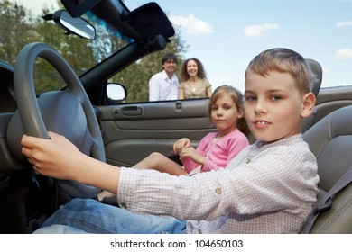 ?lose-up a boy, sitting at the wheel of cabriolet, his sister sits on a passenger seat