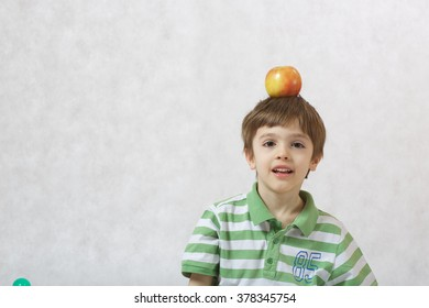 A boy of six years old  with an apple on his head. White background