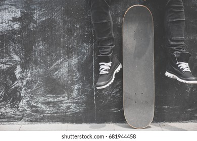Boy skater is sitting on the wall with a skateboard