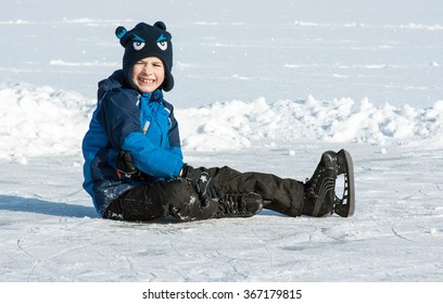 A boy in skates sitting on the ground with the face full of pain