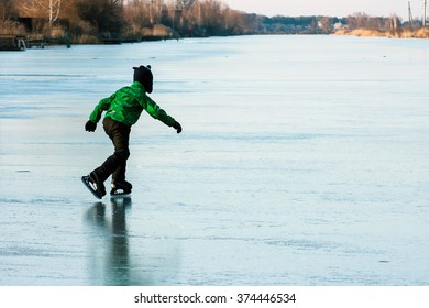 A boy skating on the frozen lake (river) in winter evening