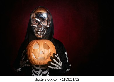 boy in skeleton costume on red background
