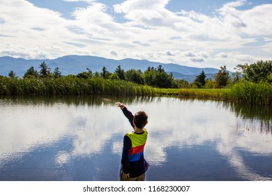 boy skimming rocks on a pond